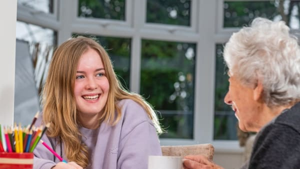 A young volunteer chats to an older person